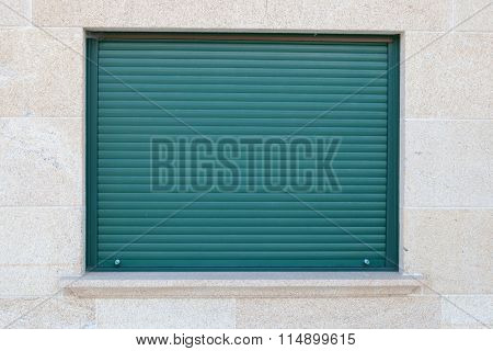 Green closed metal shutter on a window of a stone house