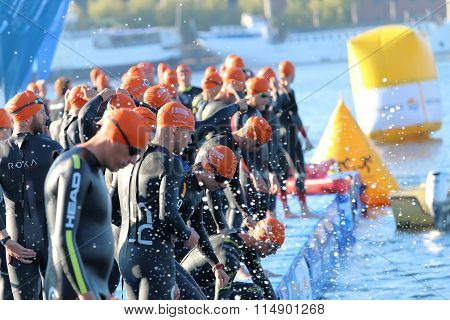 Large Group Of Male Triathletes Wearing Black Swimsuit Waiting For The Start