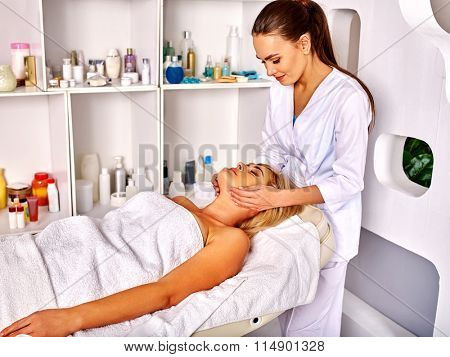 Woman middle-aged take face and neck anti-aging  massage in spa salon.