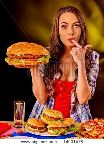 Girl taste fastfood big hamburger and pizza .