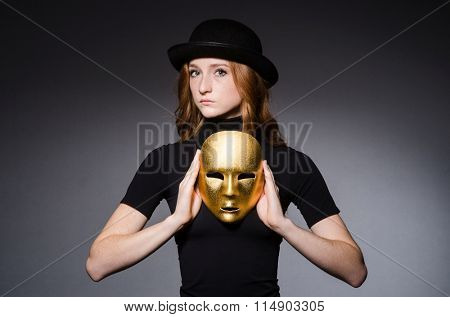 Redhead woman in hat  iwith mask in hypocrisy consept against grey background