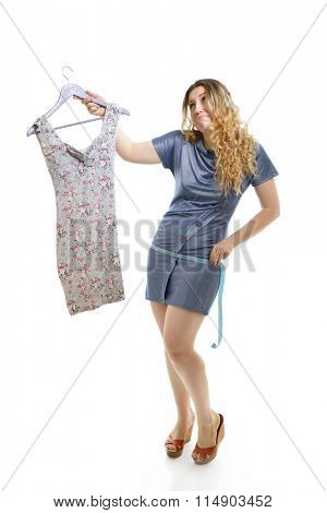Overweight young woman with measuring tape and dress over white background