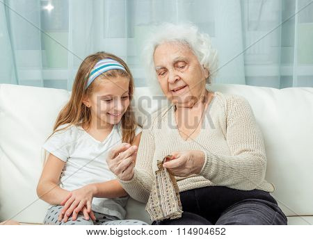 ganddaughter learning to embroider with granny on sofa