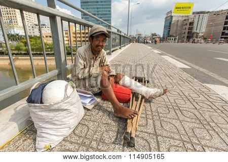 HO CHI MINH CITY, VIETNAM - JAN 14, 2016: Unidentified vietnamese beggar sitting on the street. Located in the South of Vietnam, Ho Chi Minh City is the country's largest city, population 8 million.