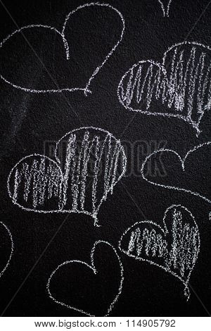 Hearts drawn in to black chalkboard