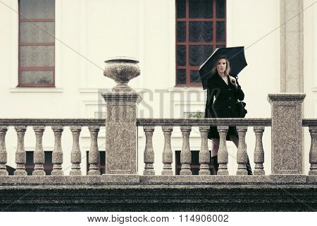 Young fashion woman in black coat with umbrella at the balustrade