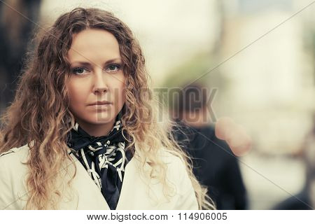 Beautiful fashion woman with long curly hairs in white coat outdoor