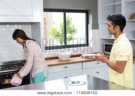 Happy couple cooking biscuits in the oven at home