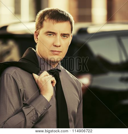 Young handsome business man next to his car