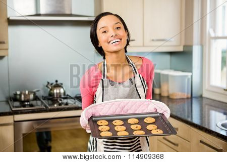 Smiling brunette showing biscuits on baking tin at home