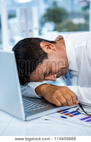 Exhausted businessman sleeping on his laptop in an office