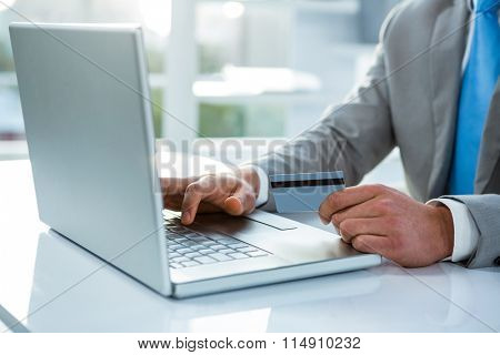 Businessman holding his credit card to pay on his laptop