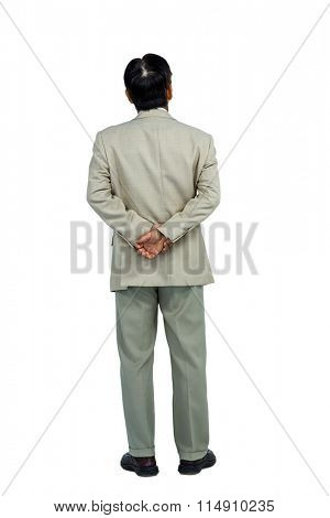 Businessman standing and looking with hands behind back on white background