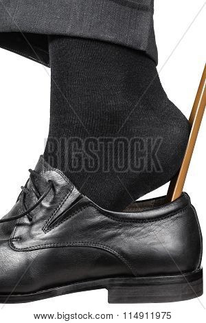 Man Puts On Black Shoe With Shoehorn Close Up