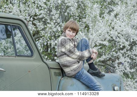 Resting teenager wearing woolly hand-knitted deer sweater sitting outdoors on old truck body at bloo