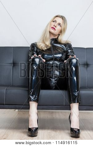 woman wearing black extravagant clothes and pumps sitting on sofa