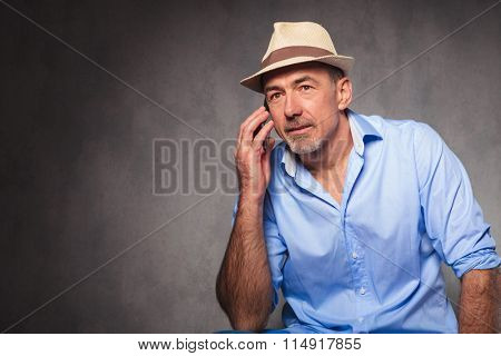 portrait of man seated and posing for the camera while looking away and talking at the phone