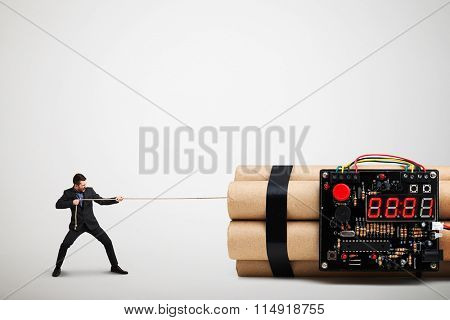 screaming businessman dragging big bomb with timer over light grey background