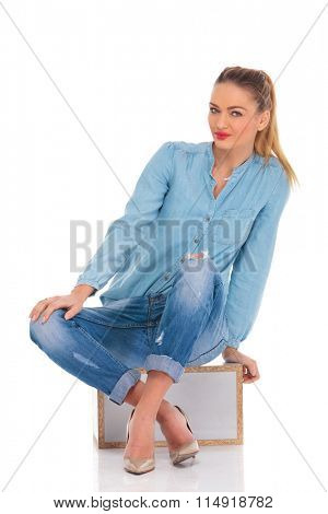beautiful blonde girl pose seated in studio background with hand on knee leaning while looking at the camera