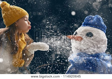 happy child girl plaing with a snowman on a snowy winter walk. Little girl enjoys the game. Child girl playing outdoors in snow. Outdoor fun for winter vacation.