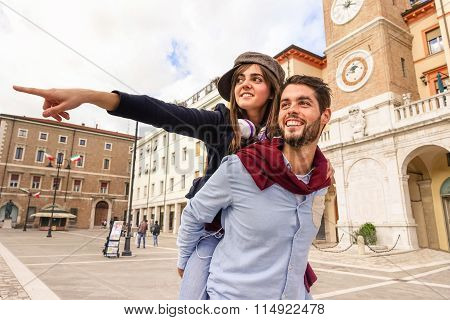 Couple Of Tourists Playing Piggyback - Two Young Cheerful Hipsters Outdoors In Old Town Central Squa
