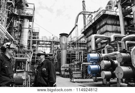 oil and gas workers at main distillery inside large refinery