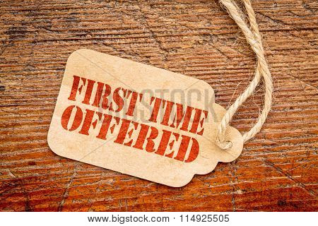 first time offered  sign - red stencil text on a paper price tag against rustic wood