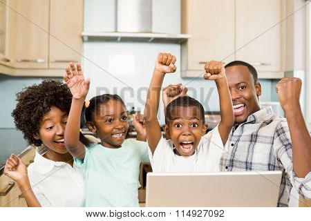Happy family triumphing in the kitchen with laptop on counter