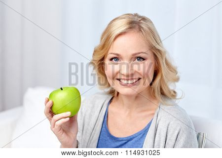 happy middle aged woman with green apple at home