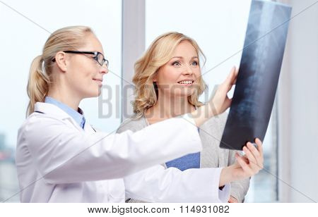 woman patient and doctor with spine x-ray scan