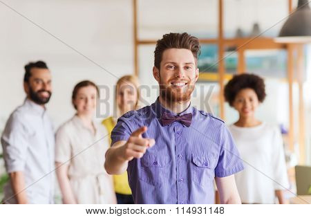 happy man pointing finger at you over office team