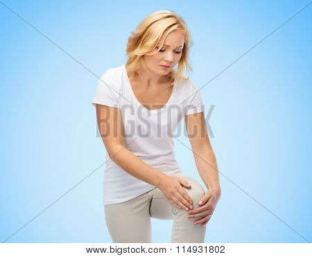 unhappy woman suffering from pain in leg