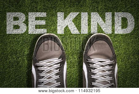 Top View of Sneakers on the grass with the text: Be Kind