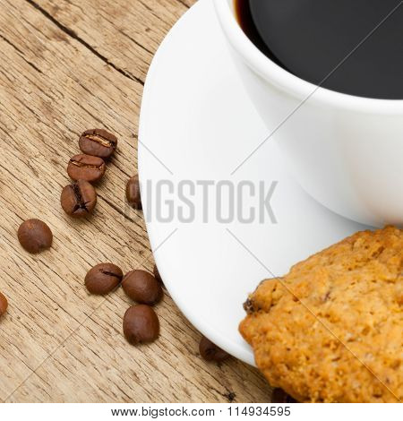 Coffee Cup And A Cookie On Wooden Table With Roasted Coffee Beans Near It