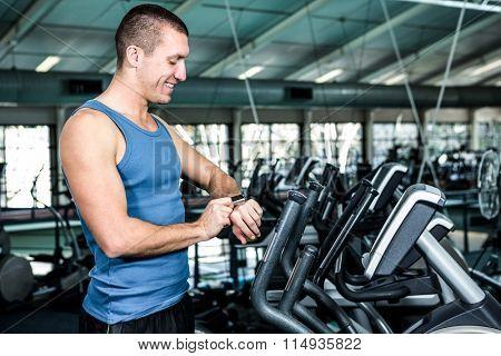 Smiling muscular man using stopwatch at gym