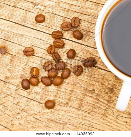 Close Up Shot Of Coffee Cup With Coffee Beans Near It
