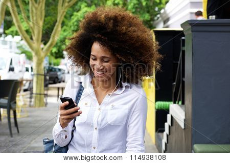 Young Black Woman Smiling With Earphones And Mobile Phone