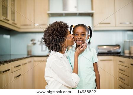 Mother kissing daughter in the kitchen