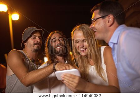 Young friends laughing at what they see on mobile