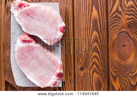 Raw Pork Loin On A Cutting Board On A Wooden Background