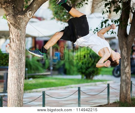 Young athlete doing extreme acrobatics outdoor