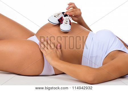 Baby's Bootees. Small Shoes For Newborn Child. Close-up Belly Of Pregnant Woman.