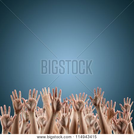 Many people's hands up on blue background.