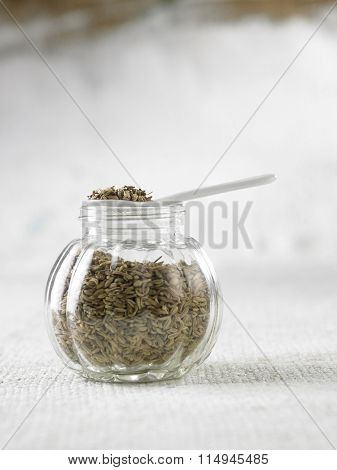 spoon of cumin on top of glass containenr
