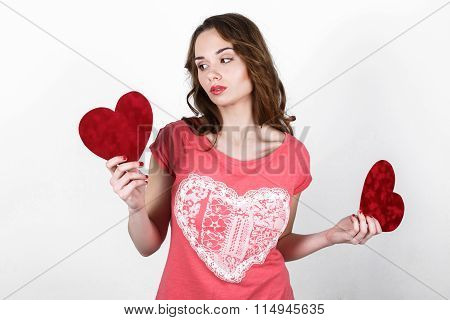 Young Beautiful Girl With Long Dark Wavy Hair In A Pink Shirt Holding  Red Heart