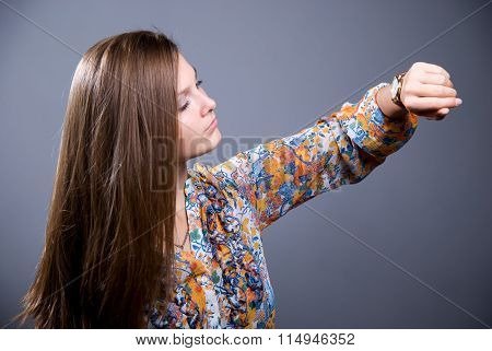 Close-up Portrait Of Young Beautiful Girl In A Bright Colored Blouse Looks At His Watch