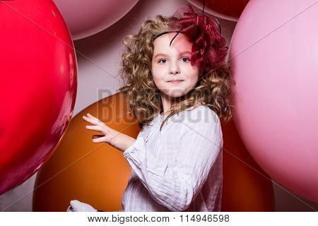 Smiling Girl In A Hat Of The Bow Against The Backdrop Of A Large Bright Airy Rubber Balls
