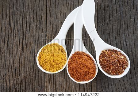 three spoons of chili powder on the wooden background