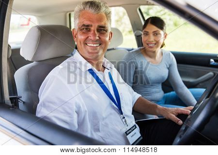 middle aged driving instructor sitting in a car with student driver