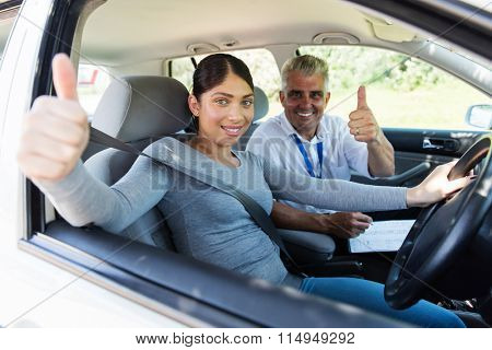 portrait of happy student driver and instructor giving thumbs up